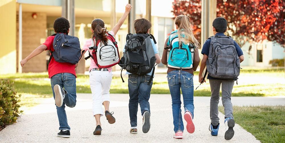 Fünf Schulkinder mit Tagessrucksäcken vor einer Schule