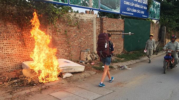 Frau mit Vaude AStrum Rucksack läuft an einem Feuer vorbei
