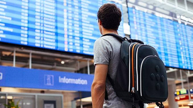 Mann mit Rucksack am Flughafen